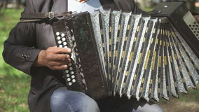 Man aged 60s plays the accordion outdoors stock video footage