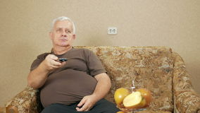 Man aged switches remote control TV channels on the couch at home. He relaxes after a hard day. holiday home concept stock footage