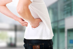 Man in agony with back pain. Young man in agony with back pain royalty free stock photography