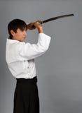 Man in aikido uniform with katana sword Royalty Free Stock Photos