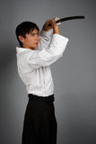 Man in aikido uniform with katana sword Stock Images