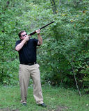 Man aimig a hunting rifle. Outdoor scene of a male aiming a shotgun Royalty Free Stock Photos