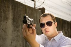 Man aiming a black gun Stock Images