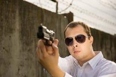 Man aiming a black gun Stock Images