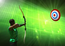 Man aiming with bow and arrow at target Stock Photos