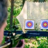 Man aiming crossbow at target Stock Photo