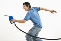 Man aiming gas nozzle. Asian young man aiming gasoline pump nozzle like a gun stock images