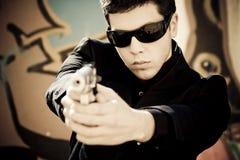 Man aiming with gun. Young man aiming at viewer with a gun Royalty Free Stock Photography