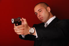 Man aiming gun. Attractive man wearing a suit aiming a gun, he has one eye closed. Red background Stock Image