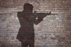 Man aiming with a gun. Man holding a gun silhouette in front of a brick wall Stock Photos