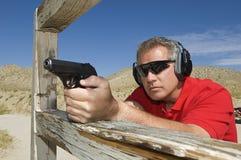 Man Aiming Hand Gun At Firing Range. Man aiming handgun at firing range during combat training Stock Photo
