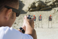 Man Aiming Hand Gun At Firing Range. Closeup of men aiming hand gun at firing range Royalty Free Stock Image