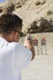 Man Aiming Hand Gun At Firing Range. Rear view of a men aiming hand gun at firing range during weapons training Stock Photography