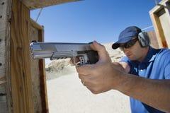 Man Aiming Hand Gun At Firing Range. During combat training Stock Photography