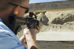 Man Aiming Machine Gun At Firing Range. Closeup of a military men aiming machine gun at firing range during weapons training Stock Images