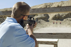 Man Aiming Machine Gun At Firing Range. Rear view of a men aiming machine gun at firing range during weapons training Stock Photos