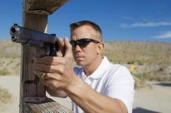 Man Aiming Machine Gun At Firing Range. Man aiming handgun at firing range during weapons training Stock Image