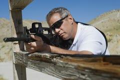 Man Aiming Machine Gun At Firing Range. In desert royalty free stock image