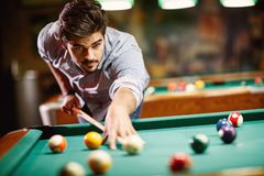 Man aiming at pool ball to billiard game. Serious man aiming at pool ball to billiard game royalty free stock images