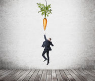 Man aiming at reward. A young businessman jumping trying to reach a painted carrot hanging from above. Concrete background. Concept of reaching an aim Royalty Free Stock Photo