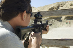 Man Aiming Rifle At Firing Range. Rear view of a military men aiming rifle at firing range stock images