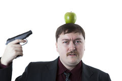Man aims at the apple on his head Royalty Free Stock Photos