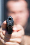 The man aims from the gun. Focus on barrel of gun. Stock Photo