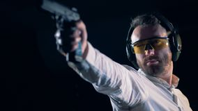 Man aims, holding a gun at a shooting gallery, shooting range. Practicing person aims with a black gun stock video