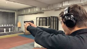 Man aims, holding a gun at a shooting gallery, shooting range. Mid shot stock video footage