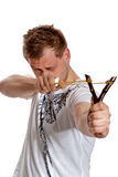 A man aims a slingshot. Young man aiming a slingshot poses in the studio on a white background Stock Photo