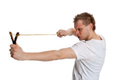 A man aims a slingshot. Young man aiming a slingshot poses in the studio on a white background Royalty Free Stock Photo