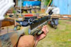 Man aims at target by crossbow or arbalest. Royalty Free Stock Photography
