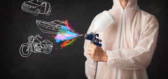 Man with airbrush spray paint with car, boat and motorcycle draw Royalty Free Stock Photo