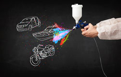 Man with airbrush spray paint with car, boat and motorcycle draw Royalty Free Stock Images