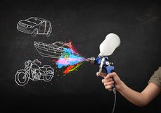 Man with airbrush spray paint with car, boat and motorcycle drawing. On dark background royalty free stock photo