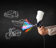 Man with airbrush spray paint with car, boat and motorcycle drawing. On dark background royalty free stock photos