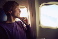 Man in airplane. Young man sitting at the window of the plane. traveler in the airplane Stock Photography