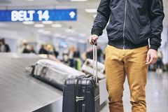 Man in airport terminal. Man traveling by airplane. Young passenger holding his suitcase near baggage claim in airport terminal Royalty Free Stock Photos