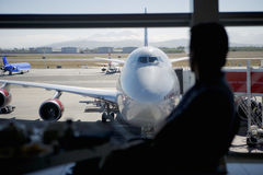 Man in airport watching airplanes on tarmac Stock Images