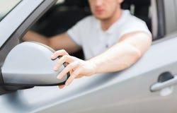 Man ajusting rear view mirror. Transportation and vehicle concept - man ajusting rear view mirror Royalty Free Stock Photography