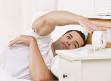 Man with Alarm Clock. A man lying in bed.  He is reaching his arm to touch an alarm clock.  He looks tired. Horizontally framed shot Stock Photo