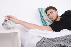 Man with alarm clock. Attractive young man with alarm clock. Indoors Royalty Free Stock Image