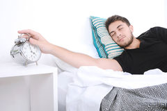 Man with alarm clock. Attractive young man with alarm clock. Indoors Stock Image