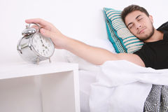 Man with alarm clock. Attractive young man with alarm clock. Indoors Royalty Free Stock Images