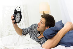 Man and alarm clock in bed Royalty Free Stock Images