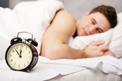 Man with alarm clock in bedroom. Royalty Free Stock Photos