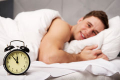 Man with alarm clock in bedroom. Stock Photography