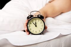 Man with alarm clock in bedroom. Stock Images