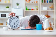 The man with alarm clock falling asleep at breakfast Stock Image