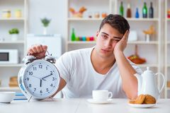 The man with alarm clock falling asleep at breakfast Royalty Free Stock Photography